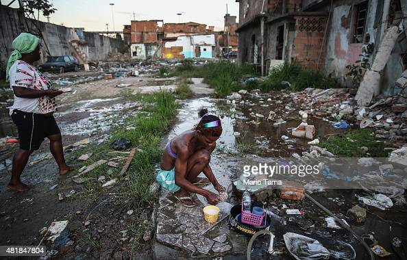 Alessandra washes kitchen items with a small hose amidst the rubble of destroyed homes in the MetroMangueira community or 'favela' located...