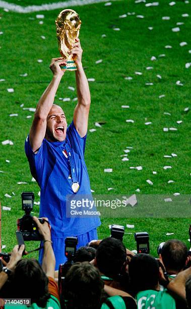 Alessandro Del Piero of Italy is surrounded by photographers as he holds the World Cup trophy aloft following his team's victory in a penalty...