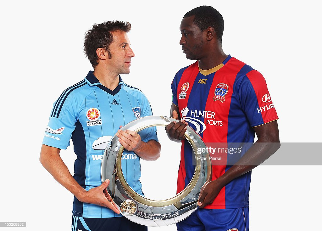 Alessandro Del Piero of Sydney FC and Emile Heskey of Newcastle Jets hold the ALeague Trophy during a 2012/13 ALeague player portrait session at...