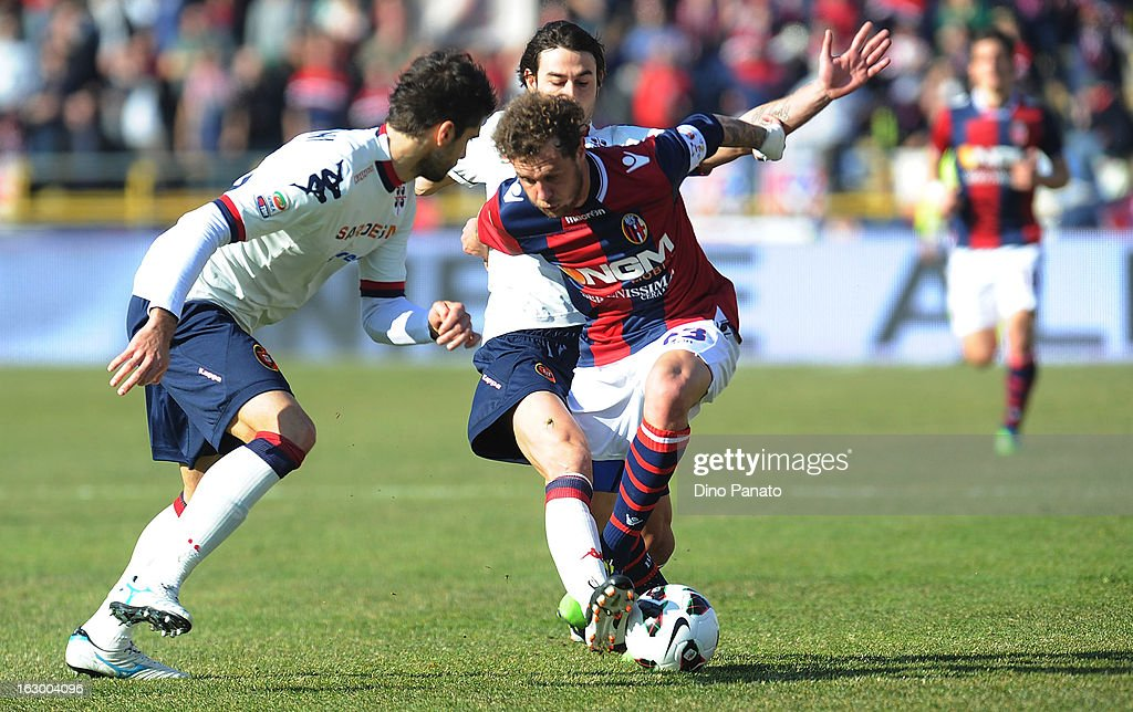 Alessandro Diamanti (R) of Bologna FC is tackled by Daniele Conti (C) of Cagliari Calcio during the Serie A match between Bologna FC and Cagliari Calcio at Stadio Renato Dall'Ara on March 3, 2013 in Bologna, Italy.