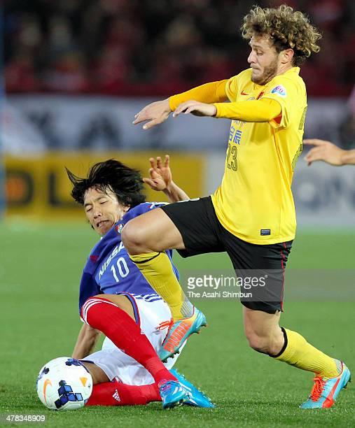 Alessandro Diamanti of Guanzhou Evergrande is tackled by Shunsuke Nakamura of Yokohama FMarinos during the AFC Champions League Group G match between...