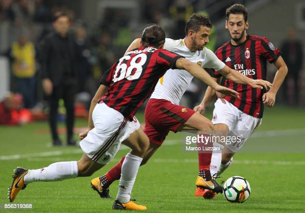 Alessandro Florenzi of AS Roma his challenged by Ricardo Rodriguez and Hakan Calhanoglu of AC Milan during the Serie A match between AC Milan and AS...
