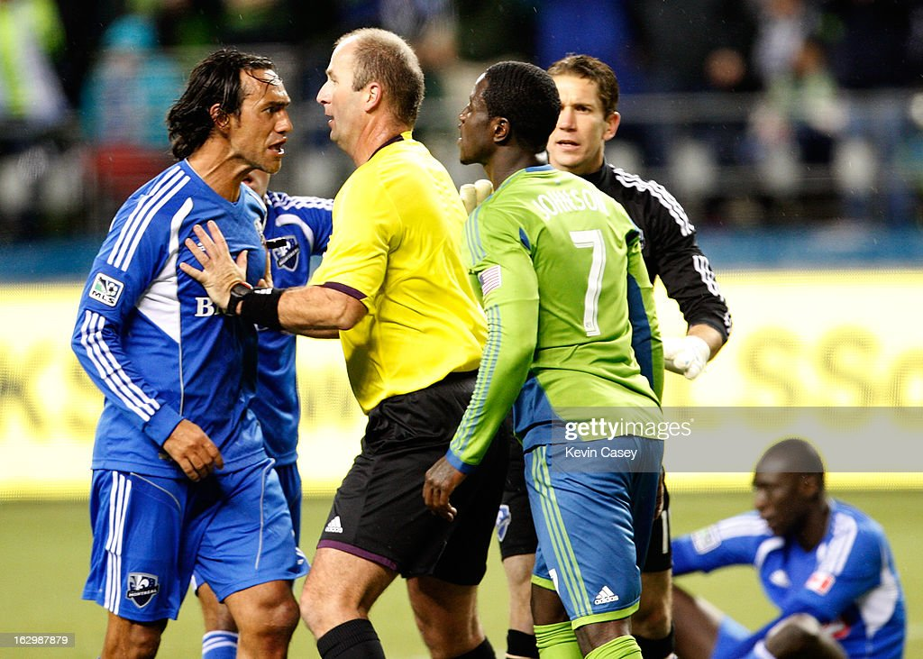 Alessandro Nesta #14, (L) of Montreal Impact, is held back by referee Silviu Petrescu as Eddie Johnson #7, of the Seattle Sounders tries to talk to him in the second half at CenturyLink Field on March 2, 2013 in Seattle, Washington.
