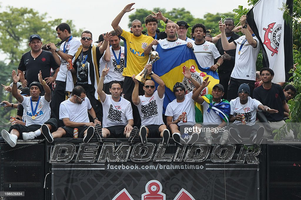 Alessandro (Front, 4th L) of Brazil's Corinthians holds the trophy of the 2012 Club World Cup during their victory parade in Sao Paulo, Brazil, on December 18, 2012. Copa Libertadores Champion Corinthians beat UEFA Champion Chelsea FC on December 16, in Yokohama, Japan. AFP PHOTO/Yasuyoshi CHIBA