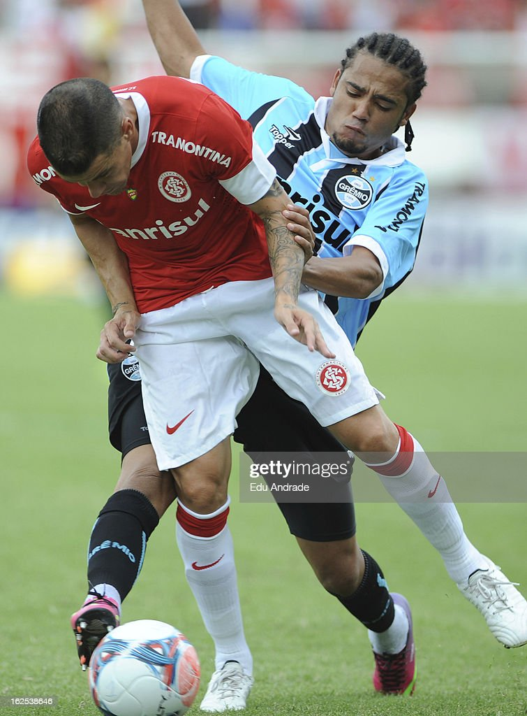D'Alessandro, of Internacional struggles for the ball with Adriano of Gremio during a match between Gremio and Internacional as part of the Gaucho championship at Centenario stadium on February 24, 2013 in Caixas Do Sul, Brazil.