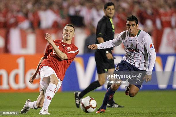 Alessandro of Internacional struggles for the ball with Patricio Araujo of Chivas during a match as part of the 2010 Copa Santander Libertadores at...