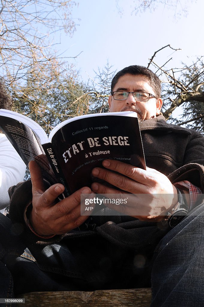 Alessandro Vargas, the next-door neighbour of late Islamist gunman Mohamed Merah, poses with his book entitled 'Etat de Siege' (State of Siege) on March 2, 2013 in Toulouse, southwestern France, a year after the assault by special police forces unit (RAID) onto their building to arrest Merah. Frenchman of Algerian descent Mohamed Merah, 23, a self-described Al-Qaeda sympathizer, who killed a rabbi, three Jewish schoolchildren and three French paratroopers, was shot dead in a police siege in Toulouse.