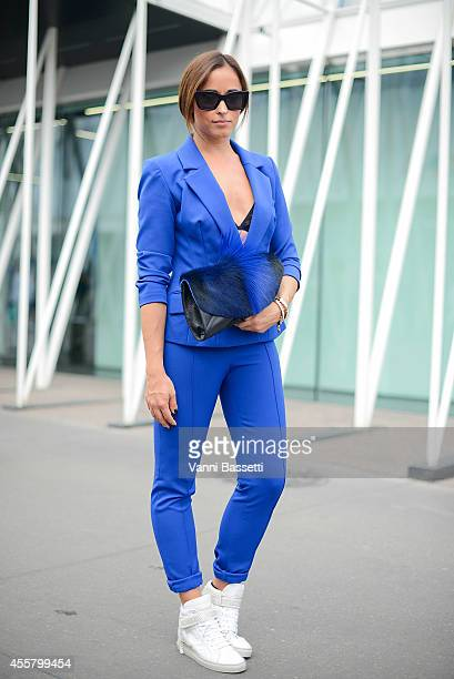 Alessia Canella poses wearing an Isabel Garcia jacket and pants Dsides shoes Ted Baker bag and Cline sunglasses on September 20 2014 in Milan Italy