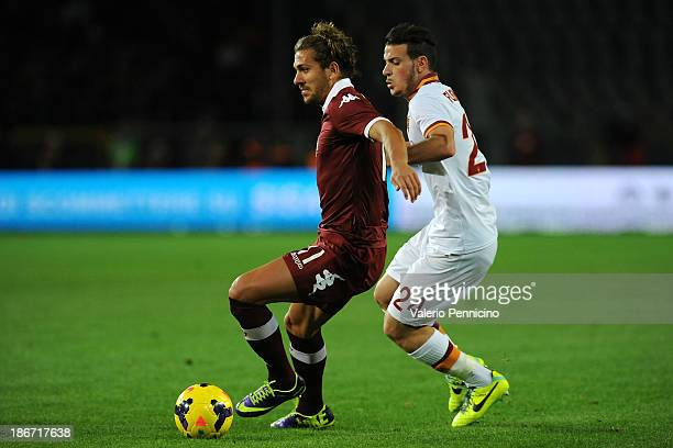 Alessio Cerci of Torino FC is challenged by Alessandro Florenzi of AS Roma during the Serie A match between Torino FC and AS Roma at Stadio Olimpico...