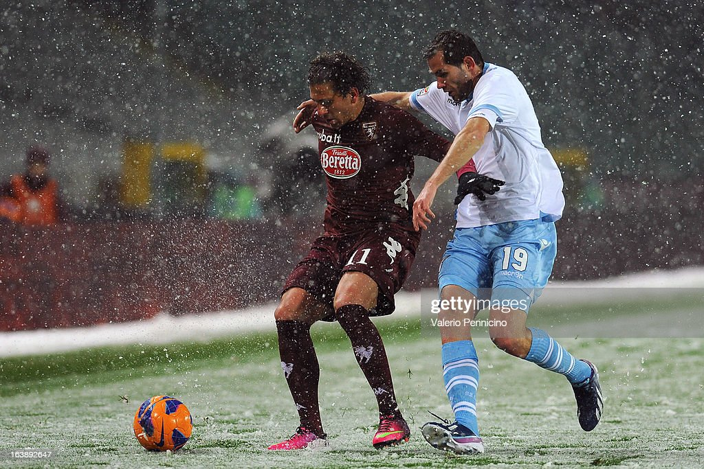Alessio Cerci (L) of Torino FC is challenged by Senad Lulic of S.S. Lazio during the Serie A match between Torino FC and S.S. Lazio at Stadio Olimpico di Torino on March 17, 2013 in Turin, Italy.