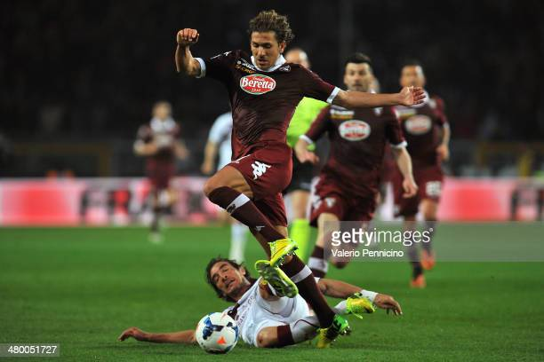 Alessio Cerci of Torino FC is tackled by Paolo Castellini of AS Livorno Calcio during the Serie A match between Torino FC and AS Livorno Calcio at...