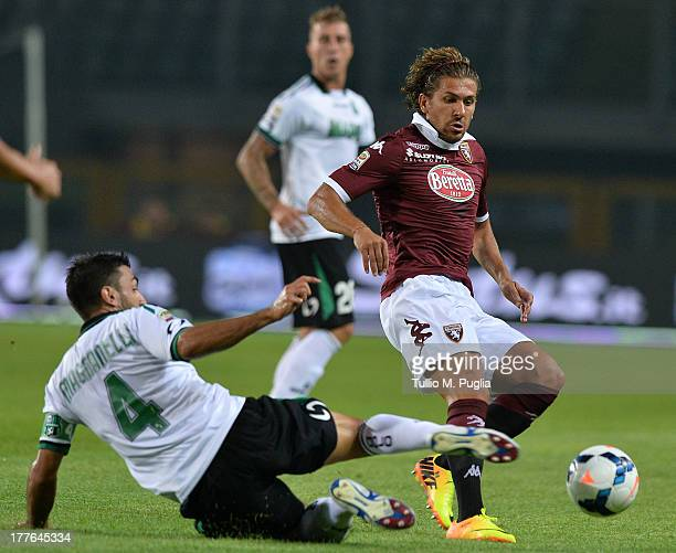 Alessio Cerci of Torino is tackled by Francesco Magnanelli of Sassuolo during the Serie A match between Torino FC and US Sassuolo Calcio at Stadio...