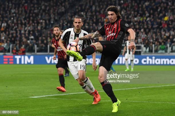 Alessio Romagnoli of AC Milan in action against Leonardo Bonucci of Juventus FC during the Serie A match between Juventus FC and AC Milan at Juventus...