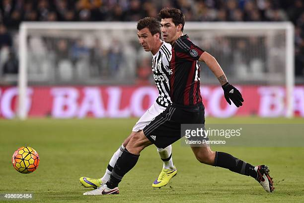 Alessio Romagnoli of AC Milan is challenged by Mario Mandzukic of Juventus FC during the Serie A match between Juventus FC and AC Milan at Juventus...