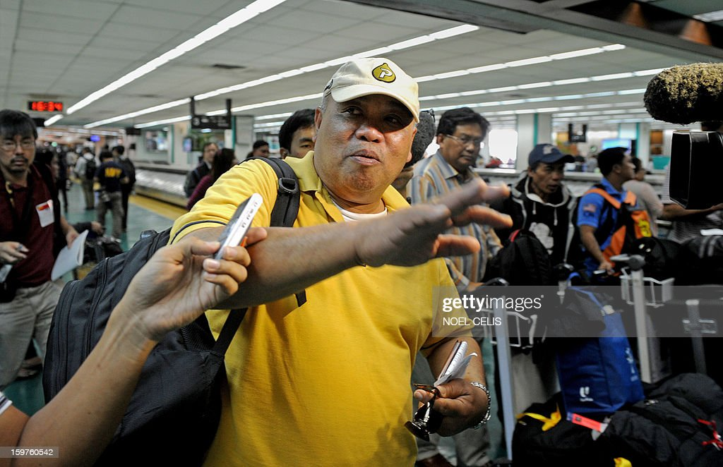 Alex Aguja (C), one of 39 Filipino overseas workers from Algeria, is interviewed by the press upon the group's arrival at Manila International Airport on January 20, 2013 after being sent home by their employer in Algeria due to security fears following an Islamic militant attack at a remote gas plant. Many of the 39 returnees said they worked for a British energy facility hundreds of kilometres from the In Amenas gas plant that was attacked by the militants last week. AFP PHOTO / NOEL CELIS