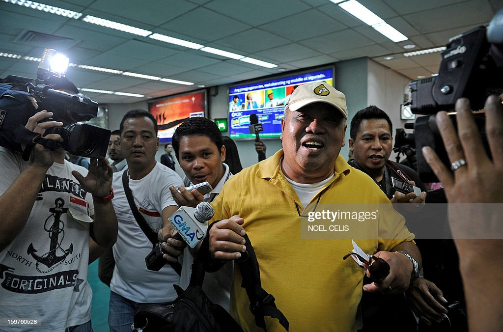 Alex Aguja (R), one of 39 Filipino overseas workers from Algeria, speaks to the press upon the group's arrival at Manila International Airport on January 20, 2013 after being sent home by their employer in Algeria due to security fears following an Islamic militant attack at a remote gas plant. Many of the 39 returnees said they worked for a British energy facility hundreds of kilometres from the In Amenas gas plant that was attacked by the militants last week.