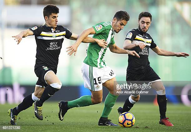 Alex Alegria of Real Betis Balompie being followed by Unai Bustinza of CD Leganes and Unai Lopez of CD Leganes during La Liga match between Real...