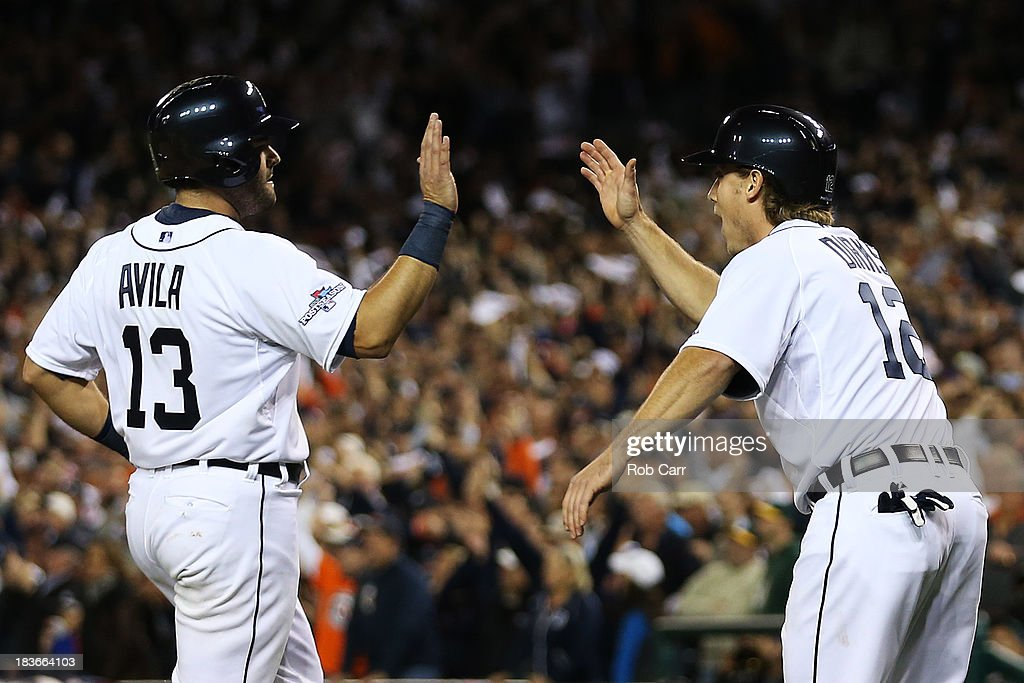 Alex Avila #13 and Andy Dirks #12 of the Detroit Tigers celebrate scoring on a double by Omar Infante #4 in the eighth inning against the Oakland Athletics during Game Four of the American League Division Series at Comerica Park on October 8, 2013 in Detroit, Michigan.