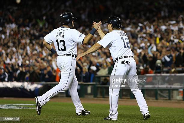 Alex Avila and Andy Dirks of the Detroit Tigers celebrate scoring on a double by Omar Infante in the eighth inning against the Oakland Athletics...