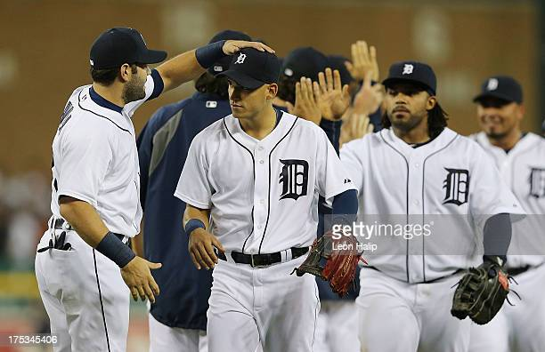 Alex Avila of the Detroit Tigers celebrates a win over the Chicago White Sox with newly acquired infielder Jose Iglesias during the game at Comerica...