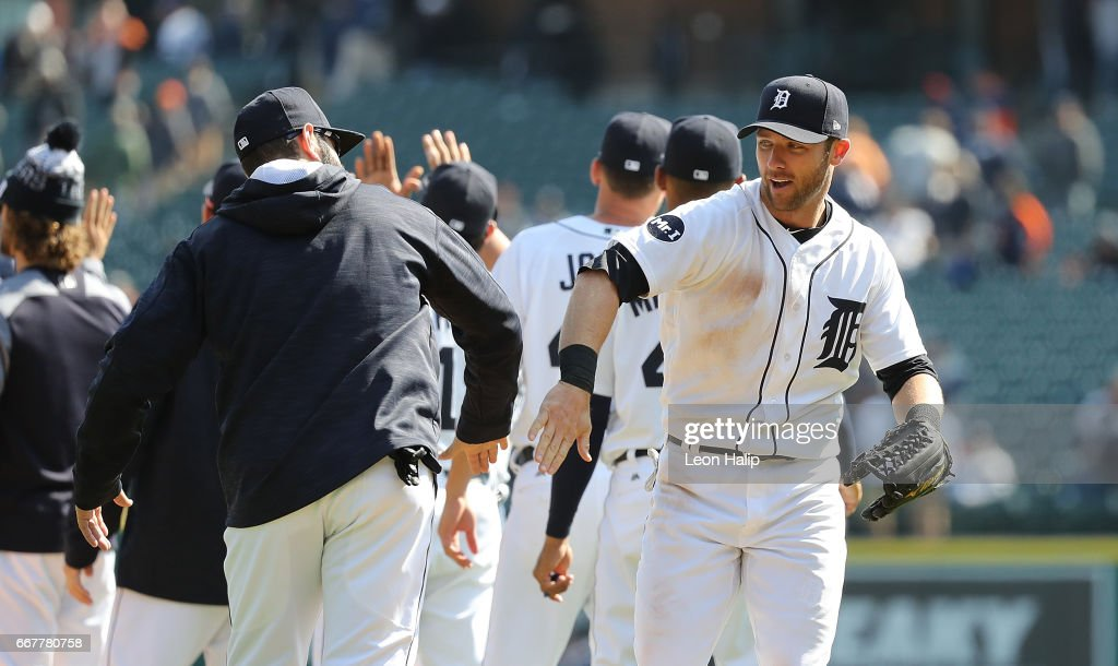 Alex Avila #31 of the Detroit Tigers congratulates teammate Andrew Romine #17 after the win over the Minnesota Twins on April 12, 2017 at Comerica Park in Detroit, Michigan. The Tigers defeated the Twins 5-3.