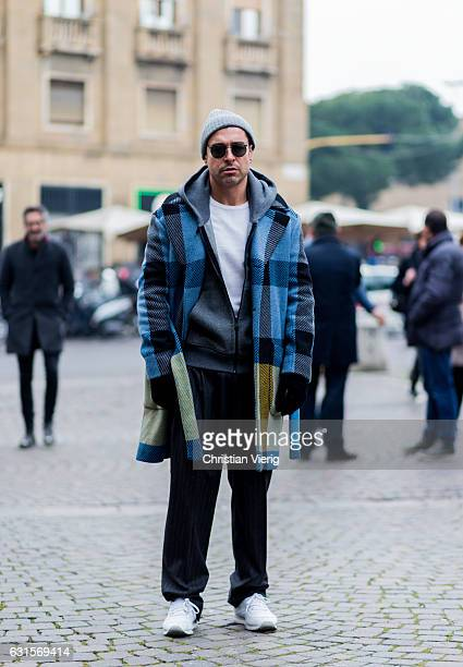 Alex Badia is wearing a checked coat beanie zip jacket wide leg striped pants sneaker on January 12 2017 in Florence Italy