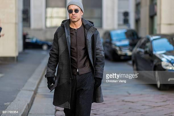 Alex Badia is wearing a grey coat black pants beanie zip jacket during Milan Men's Fashion Week Fall/Winter 2017/18 at Salvatore Ferragamo on January...