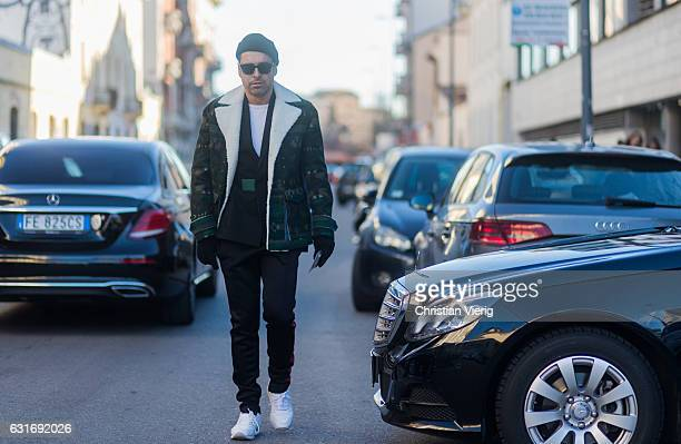 Alex Badia is wearing a inner lining jacket camouflage jogger pnats beanie gloves seen at Diesel during Milan Men's Fashion Week Fall/Winter 2017/18...