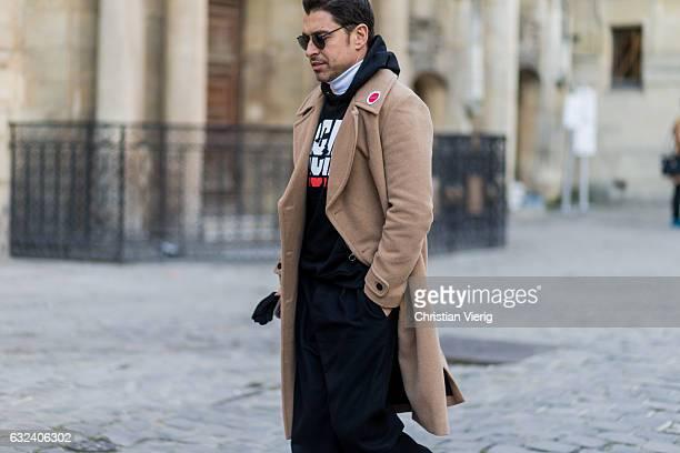 Alex Badia wearing a beige coat black hoody black jogger pants outside Paul Smith on January 22 2017 in Paris France
