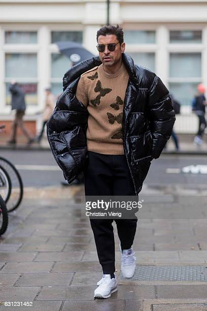 Alex Badia wearing a black down feather jacket brown knit black pants white sneaker during London Fashion Week Men's January 2017 collections at JW...