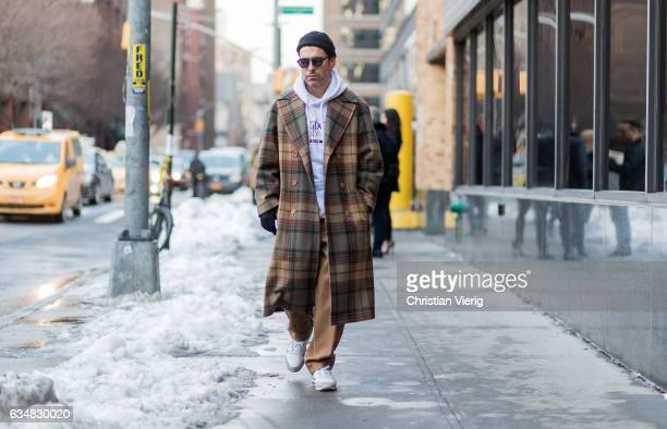 Alex Badia wearing a checked coat white hoody black beanie sunglasses beige pants white sneaker outside Jonathan Simkhai on February 11 2017 in New...