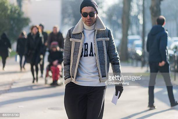 Alex Badia wearing a inner lining jacket wide leg pants white turtleneck sweater beanie outside Dior Homme on January 21 2017 in Paris France