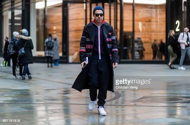 Alex Badia wearing a navy beanie black wool coat black pants black zipper jacket during London Fashion Week Men's January 2017 collections at Lou...