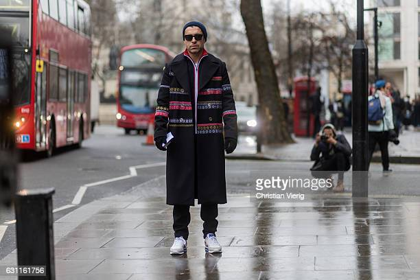 Alex Badia wearing a navy beanie sunglasses black coat and zip jacket during London Fashion Week Men's January 2017 collections at Katy Eary on...