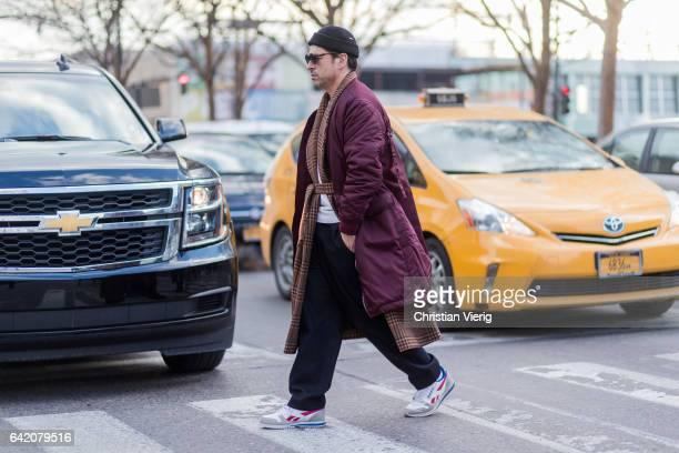 Alex Badia wearing a purple coat beanie outside Yeezy Season 5 on February 15 2017 in New York City