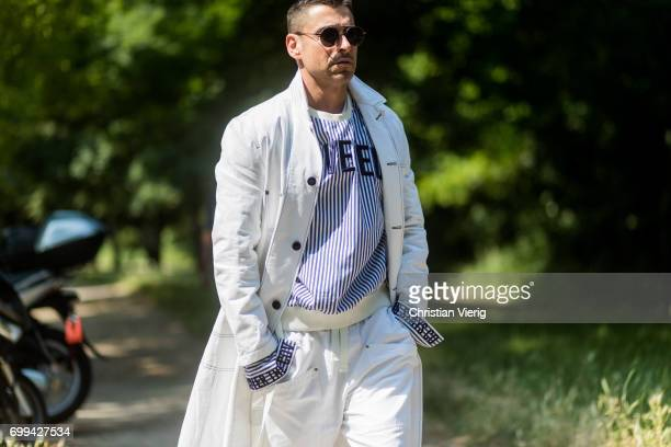 Alex Badia wearing creme pants coat and striped knit outside Balenciaga during Paris Fashion Week Menswear Spring/Summer 2018 on June 21 2017 in...
