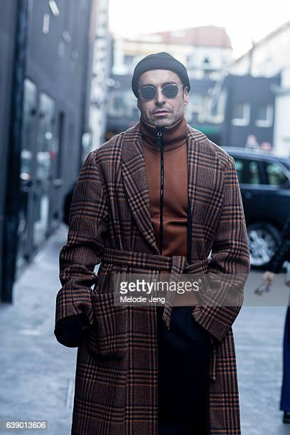 Alex Badia wears a Dries Van Noten belted tartan coat and a Burberry orange turtleneck during Milan Men's Fashion Week Fall/Winter 2017/18 on January...