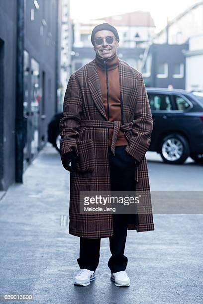 Alex Badia wears a Dries Van Noten belted tartan coat Burberry orange turtleneck and AMI trousers during Milan Men's Fashion Week Fall/Winter 2017/18...