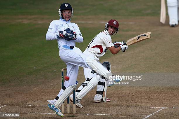 Alex Barrow of Somerset looks back with wicketkeeper Thomas Poynton of Derbyshire as he edges a catch to Wayne Madsen off the bowling of Antonio...