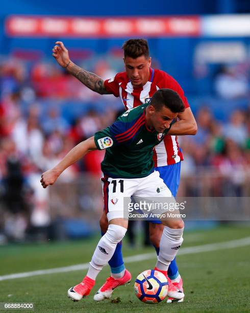 Alex Berenguer of CA Osasuna competes for the ball with Jose Maria Gimenez of Atletico de Madrid during the La Liga match between Club Atletico de...