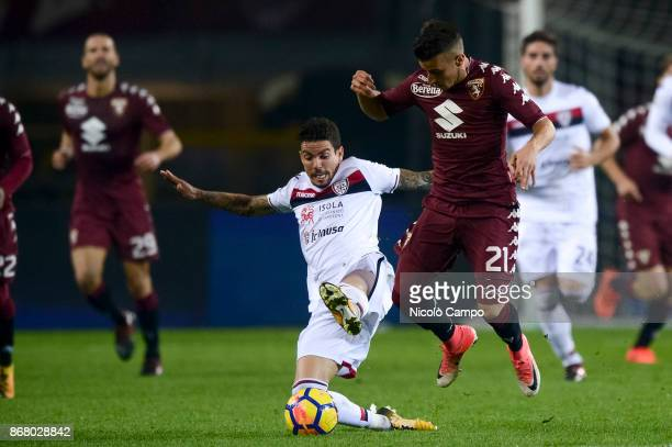 Alex Berenguer of Torino FC is tackled by Diego Farias of Cagliari Calcio during the Serie A football match between Torino FC and Cagliari Calcio...