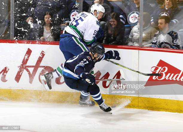 Alex Biega of the Vancouver Canucks jumps up to avoid a check along the boards by Nikolaj Ehlers of the Winnipeg Jets during second period action at...
