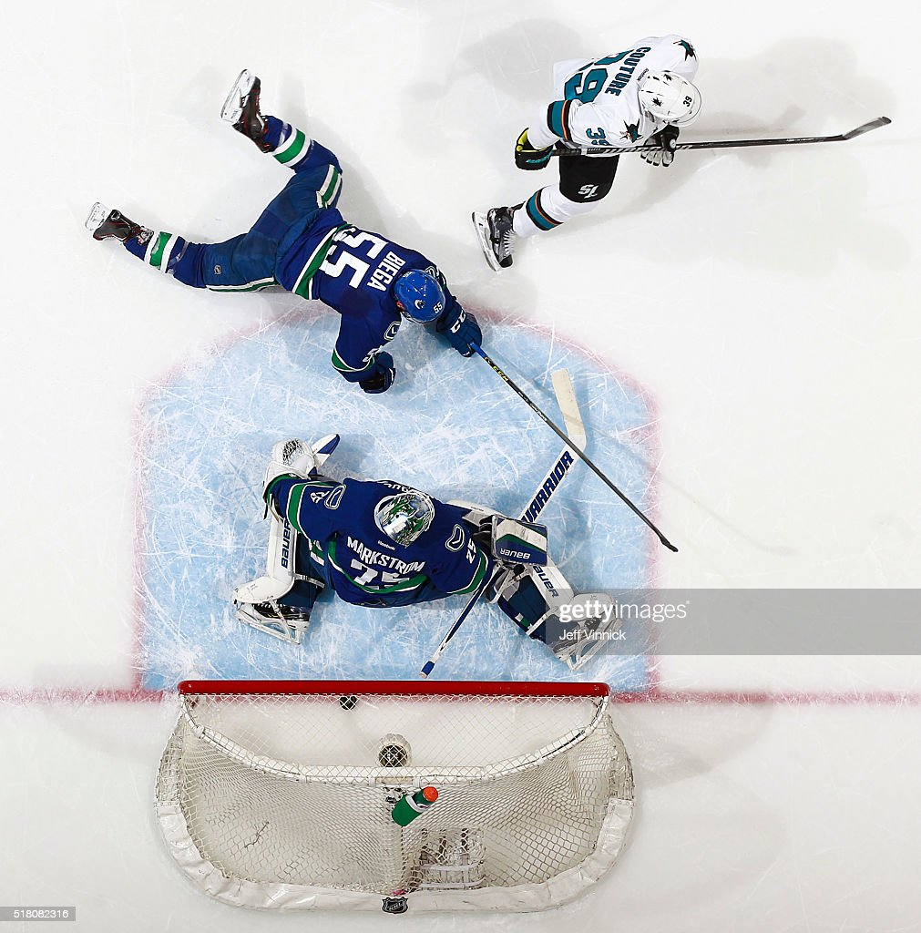 Alex Biega #55 of the Vancouver Canucks watches as Logan Couture #39 of the San Jose Sharks score on Jacob Markstrom #25 of the Canucks during their NHL game at Rogers Arena March 29, 2016 in Vancouver, British Columbia, Canada. San Jose won 4-1.