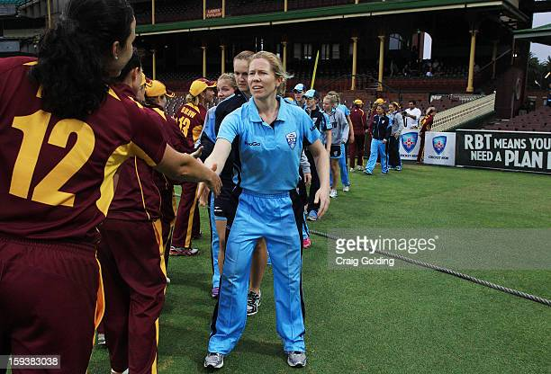 Alex Blackwell and the Breakers shake hands with the Fire players at after play was called off due to rain during the WNCL Final match between the...