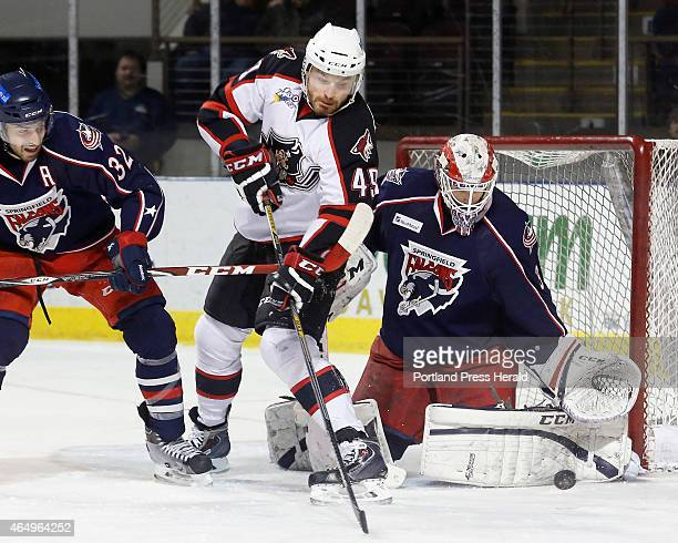 Alex Bolduc of Portland tries to slap the puck past Anton Forsberg of Springfield during the first period as Springfield's Frederic St Denis defends