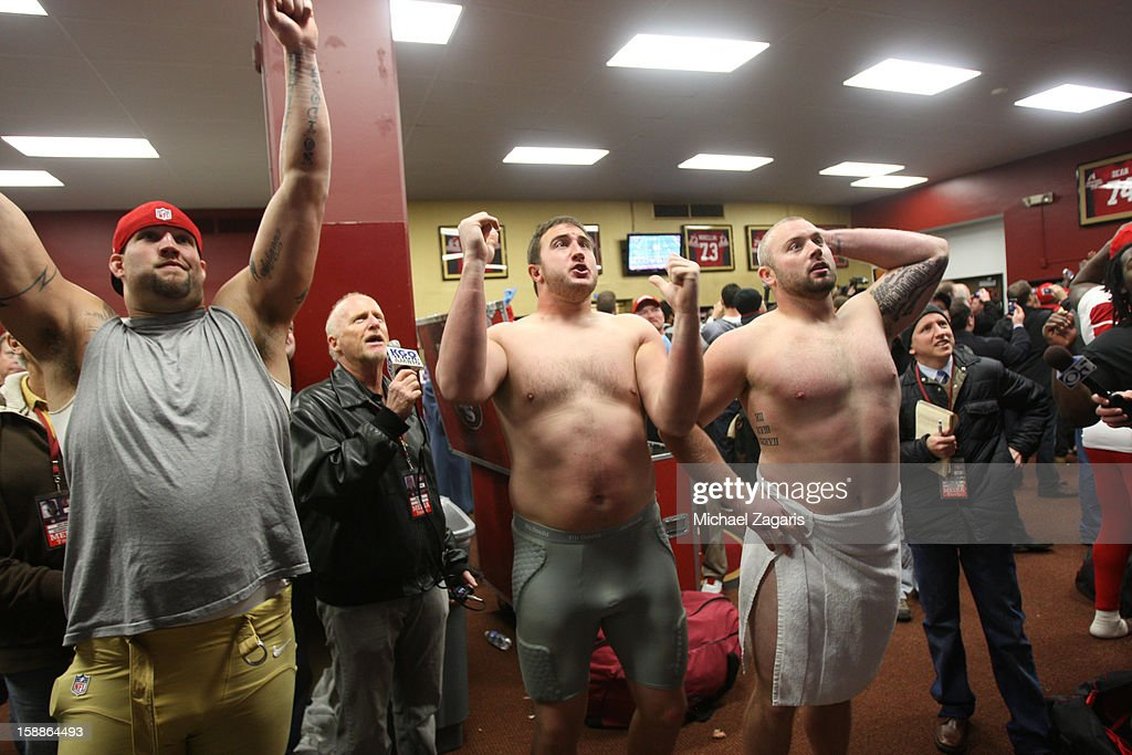 Alex Boone #75, Joe Staley #74 and Daniel Kilgore #67 of the San Francisco 49ers celebrate as the Vikings defeat the Packers on TV in the locker room following the game against the Arizona Cardinals at Candlestick Park on December 30, 2012 in San Francisco, California. The 49ers defeated the Cardinals 27-13.