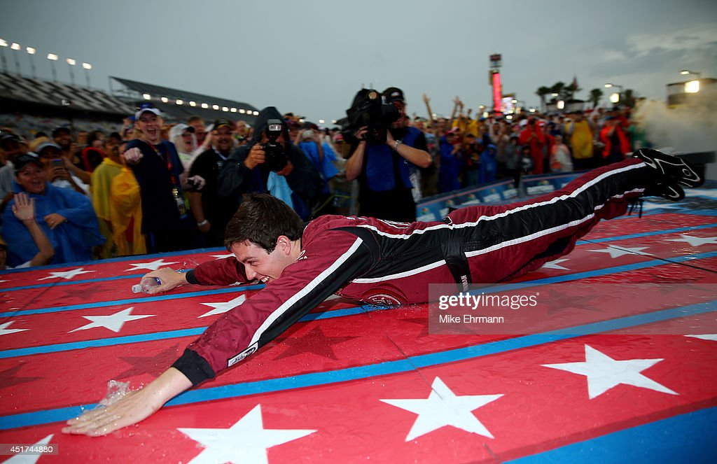 Alex Bowman, driver of the #23 Dr. Pepper Toyota, slides down the stage during driver introductions prior to the NASCAR Sprint Cup Series Coke Zero 400 at Daytona International Speedway on July 5, 2014 in Daytona Beach, Florida.