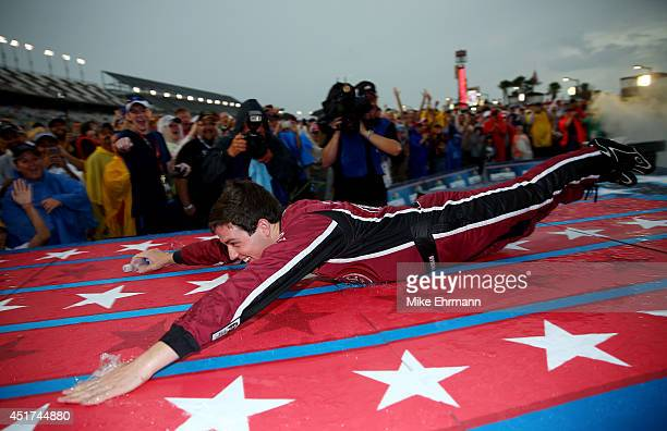 Alex Bowman driver of the Dr Pepper Toyota slides down the stage during driver introductions prior to the NASCAR Sprint Cup Series Coke Zero 400 at...
