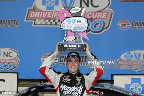 Alex Bowman driver of the HendrickCarscom Chevrolet celebrates with the trophy in Victory Lane after winning the NASCAR XFINITY Series Drive for the...