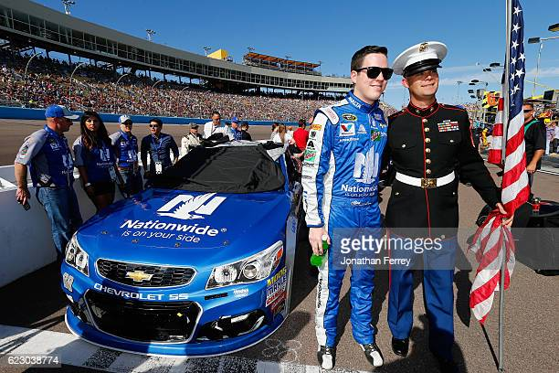 Alex Bowman driver of the Nationwide Chevrolet poses for a photo with a military serviceman on pit road prior to the NASCAR Sprint Cup Series CanAm...